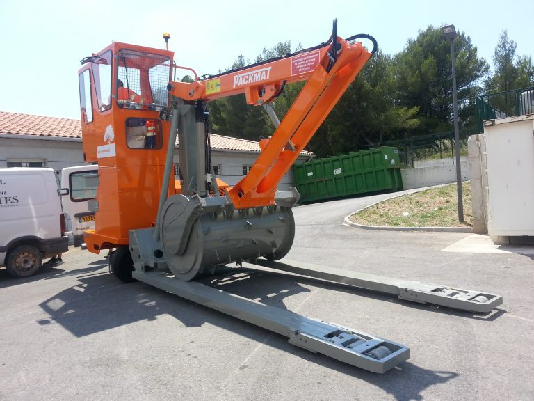 PK421 compacteur porteur avec fourche de levage sur site déchèterie permettant la compaction des bennes de déchets packmat system